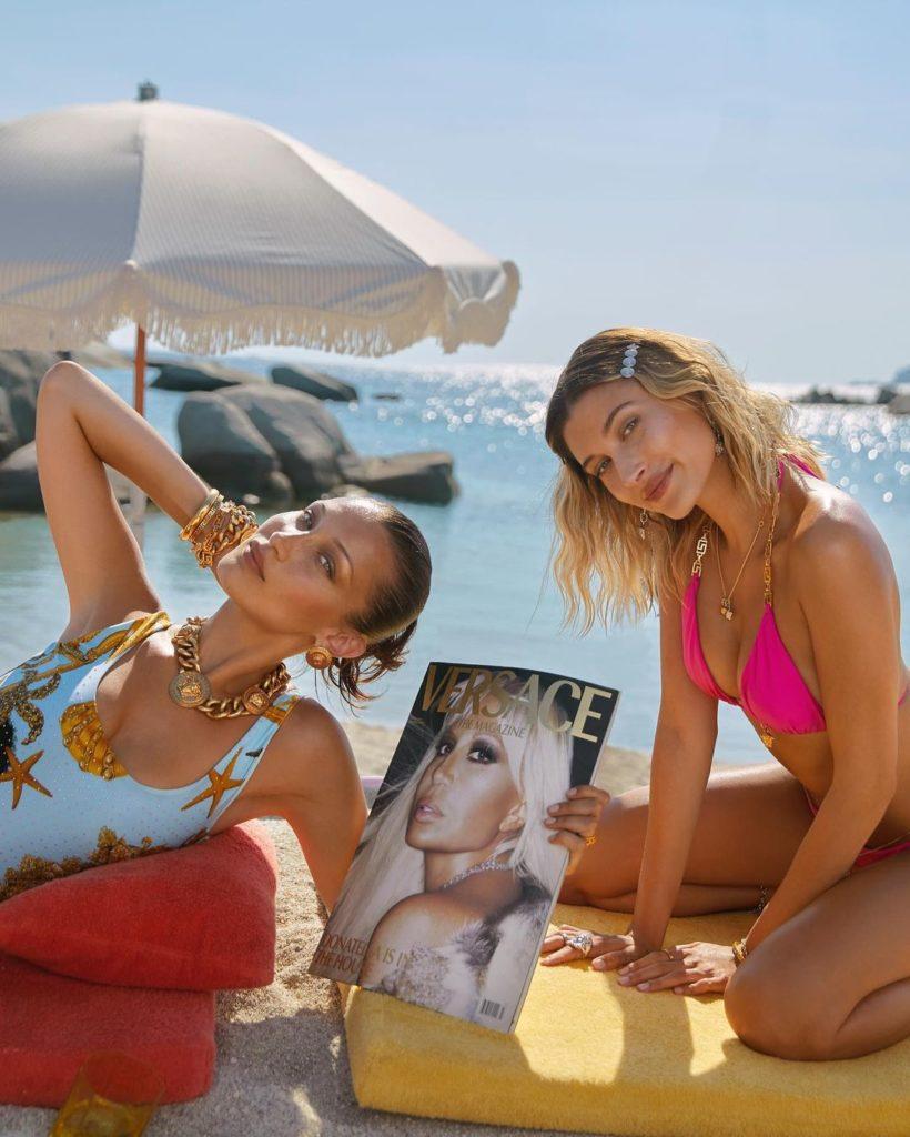 Фотомодели Белла Хадид и Хейли Бибер на пляже в купальниках с журналом Версаче.
