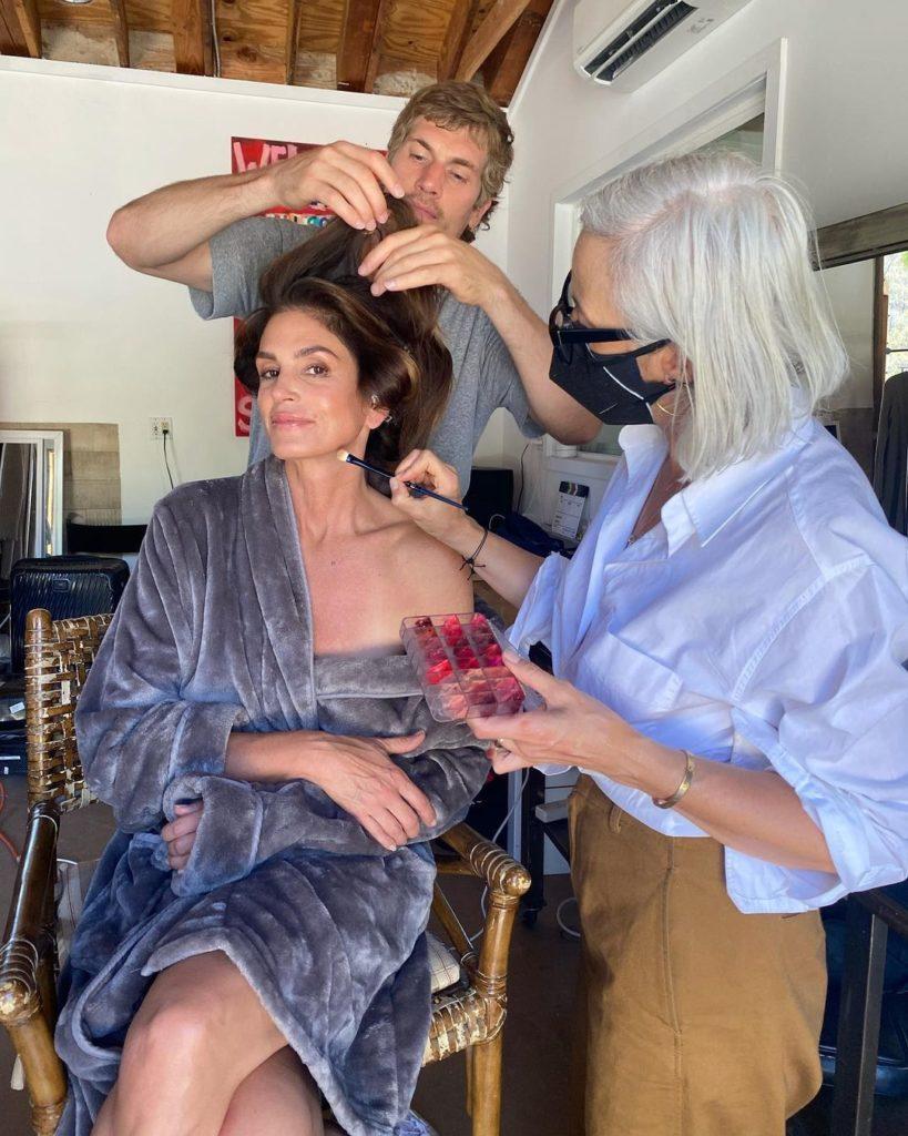 Модели Сидни Кроуфорд укладывают прическу и наносят макияж.