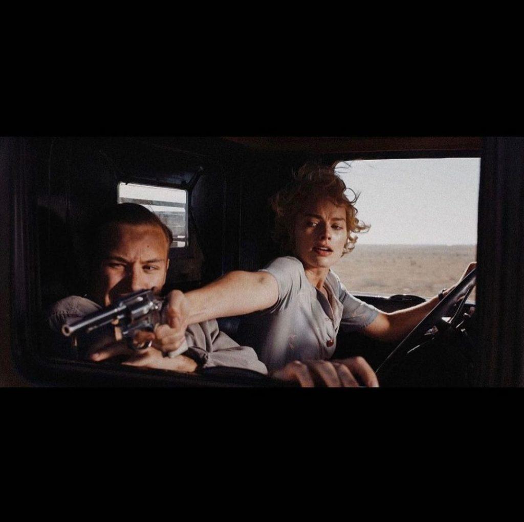 Кадр из фильма Страна грез. Киноактриса Марго Робби с револьвером в машине.