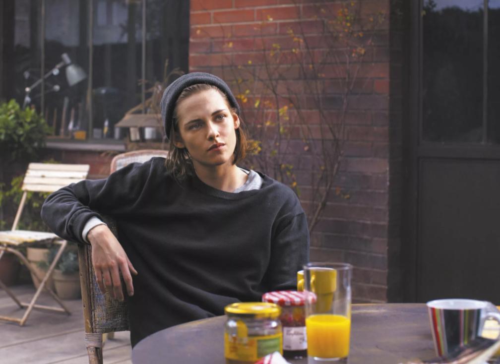 Киноактриса Кристен Стюарт за столиком в кафе.