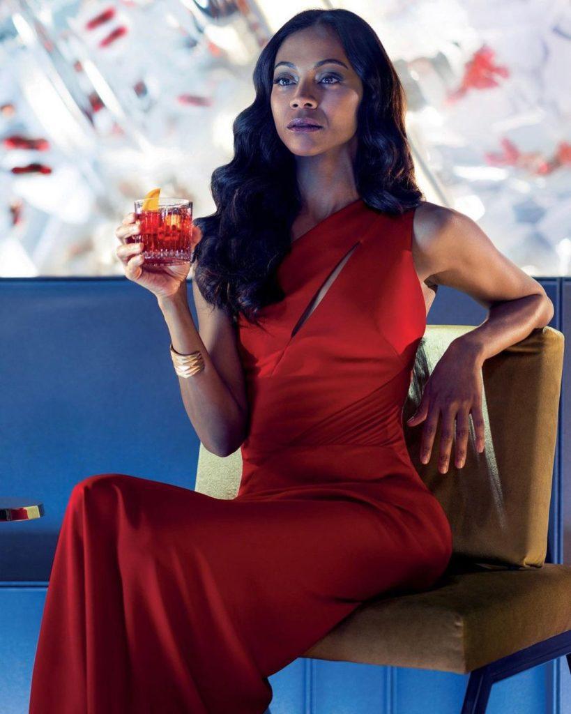 Актриса Зои Салдана с бокалом в руке и в красном платье.