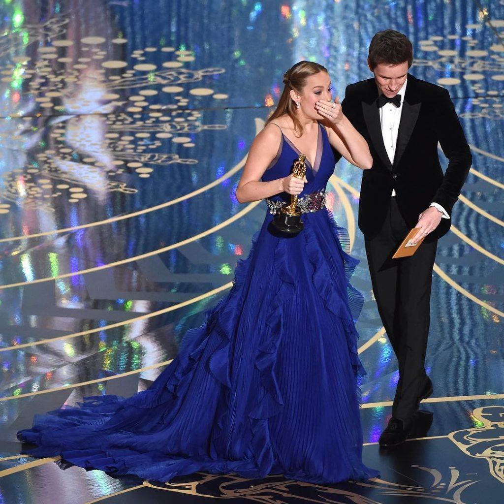 """Вручение 88 премии Оскар. Актриса в синем платье держит статуэтку и закрывает лицо руками от счастья. Актрисы получившие """"Оскар"""""""