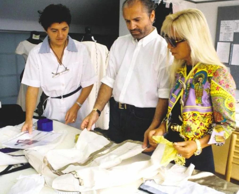 Джанни Версаче в мастерской смотрит одежду.
