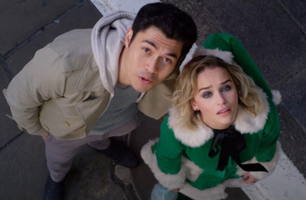 актриса Эмилия Кларк в зеленом костюме рождественского эльфа и актер Генри Голдинг смотрят на небо.
