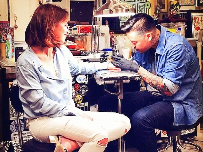 актриса Эмилия Кларк делает тату в салоне.