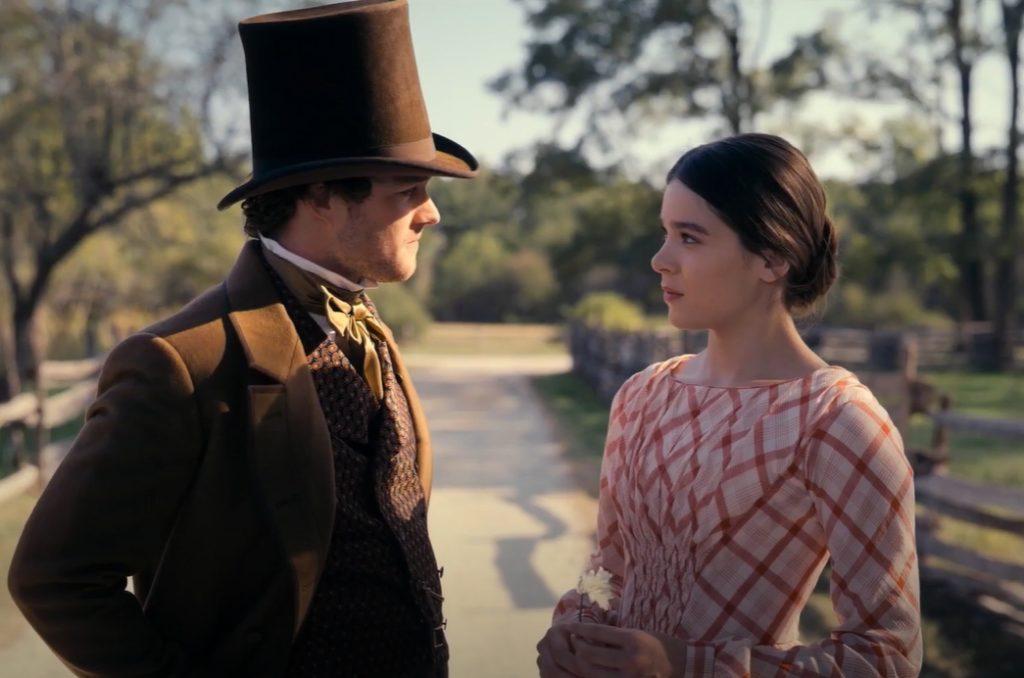 Хейли Стайнфелд в роли в сериале Дикинсон и молодой человек в высокой шляпе.