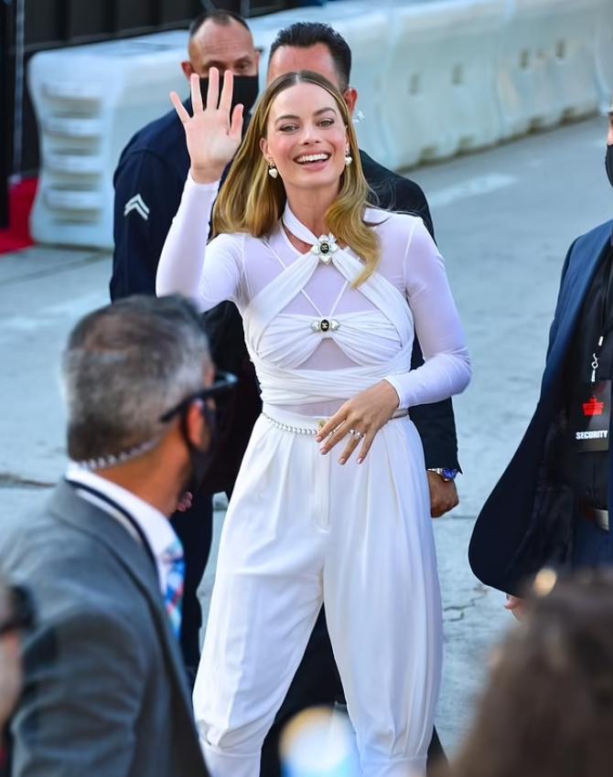 Марго Робби в белом костюме машет рукой.