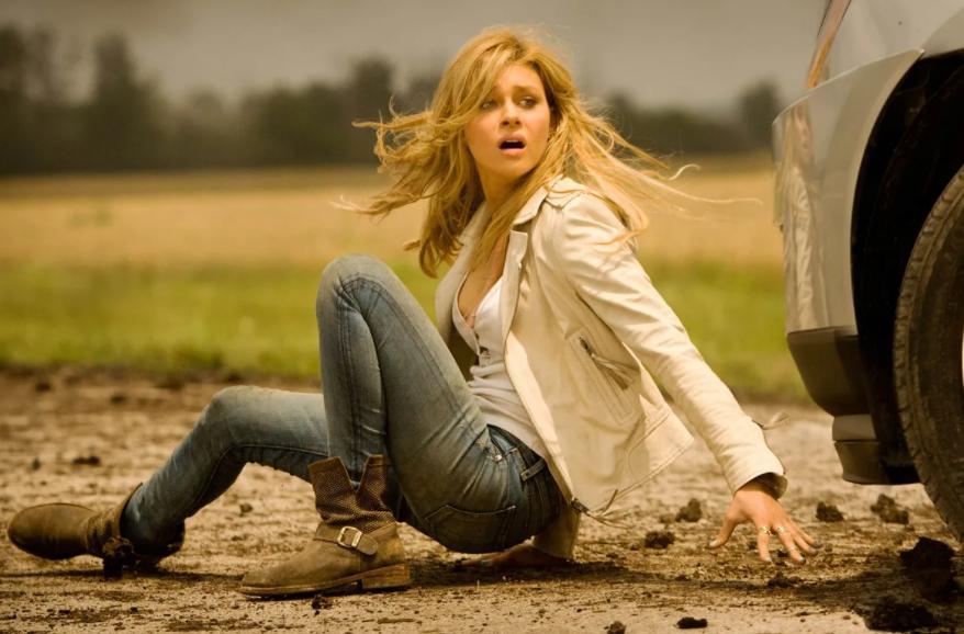 Тесса Йегер в белой куртке падает в грязь возле машины. Фильм Трансформеры.