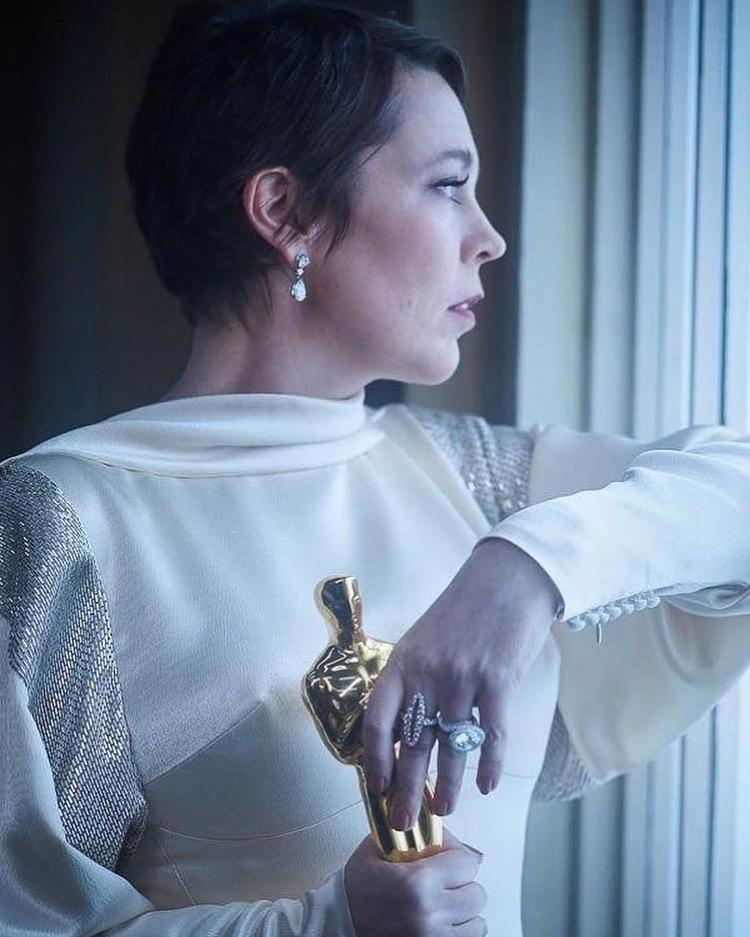 """Актриса в белом платье со статуэткой Оскара смотрит в окно. Актрисы получившие """"Оскар"""""""