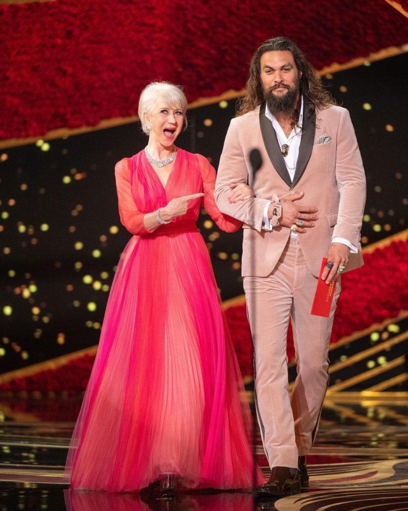 Ведущие премии Оскар. Актриса в красно-розовом платье и Джейсон Момоа с конвертом в руке.