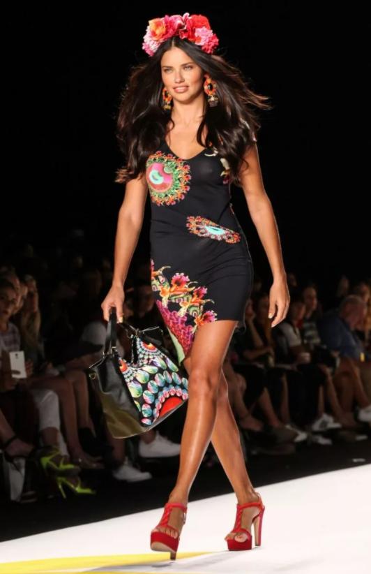 Бразильская модель адриана Лима идет по подиуму с сумкой в руках.