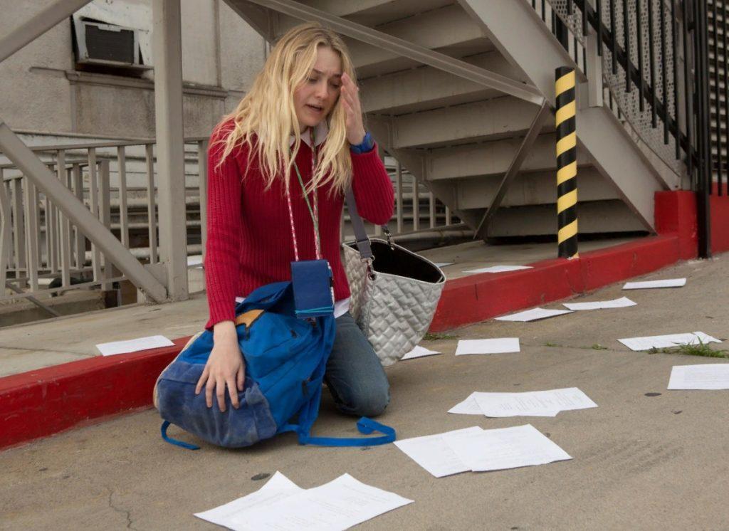 Актриса Дакота Фаннинг сидит на асфальте и собирает бумаги.