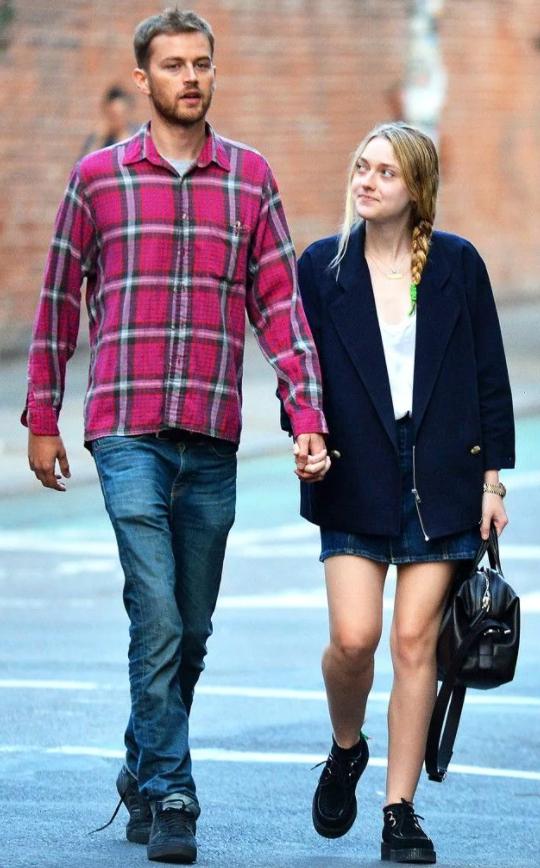 Актриса Дакота Фаннинг и ее парень идут по улице взявшись за руки.