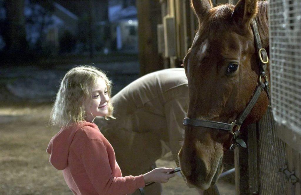 Актриса Дакота Фаннинг в детстве кормит лошадку.