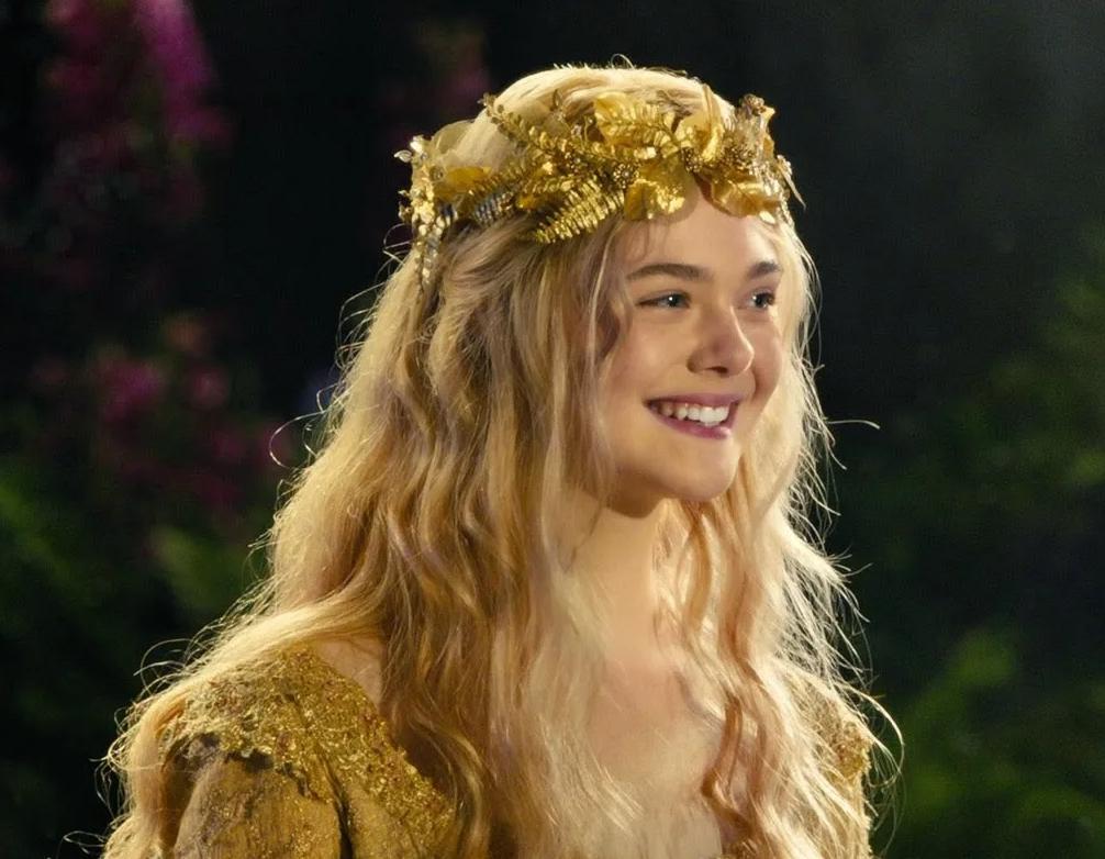 Актриса Эль Фаннинг с венком на голове. Улыбается.