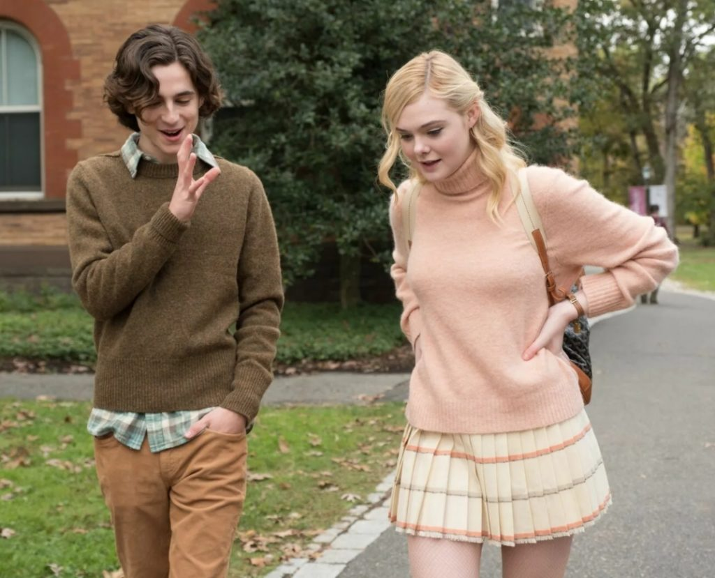 Актриса Эль Фаннинг идет по улице, разговаривая с парнем.