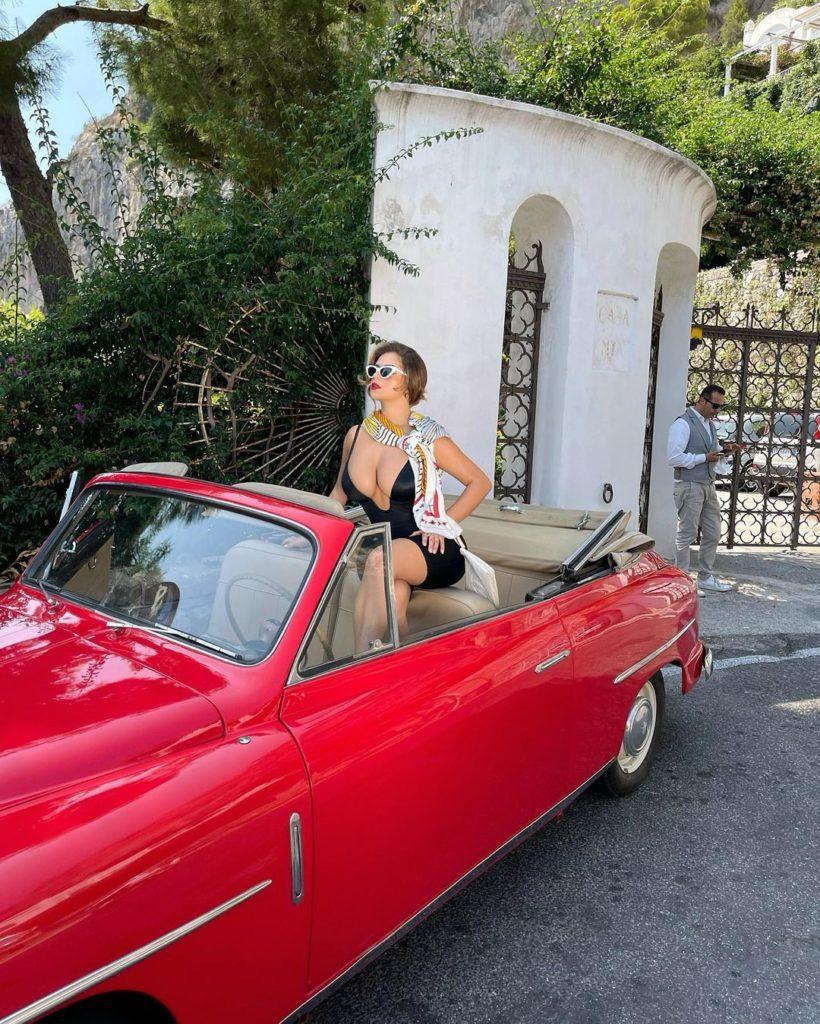 Модель Деми Роуз в красном кадиллаке.
