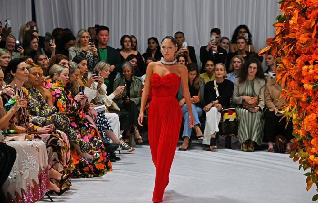 Лила Мосс идет по подиуму на лондонской недели моды в красном костюме.