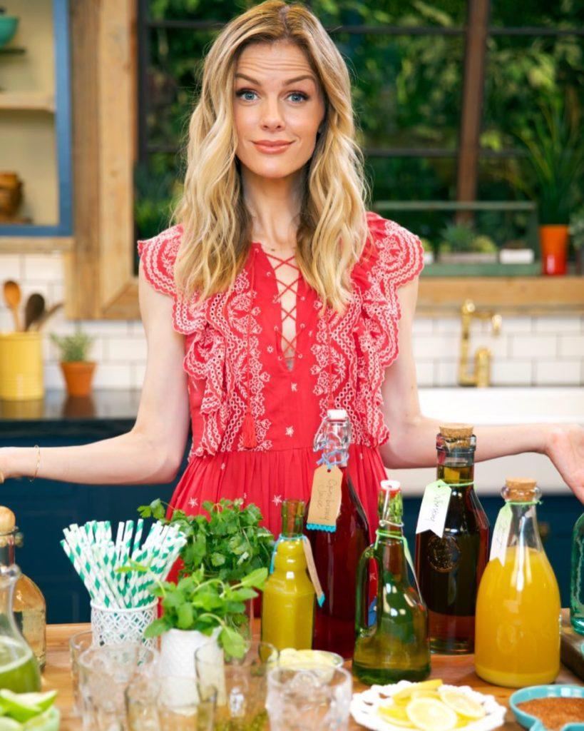Модель и актриса Бруклин Деккер разводит руками. На столе приправы и соусы в бутылках.