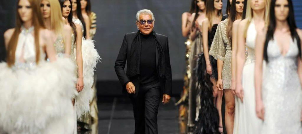модельер Роберто Кавалли в окружении моделей на подиуме.
